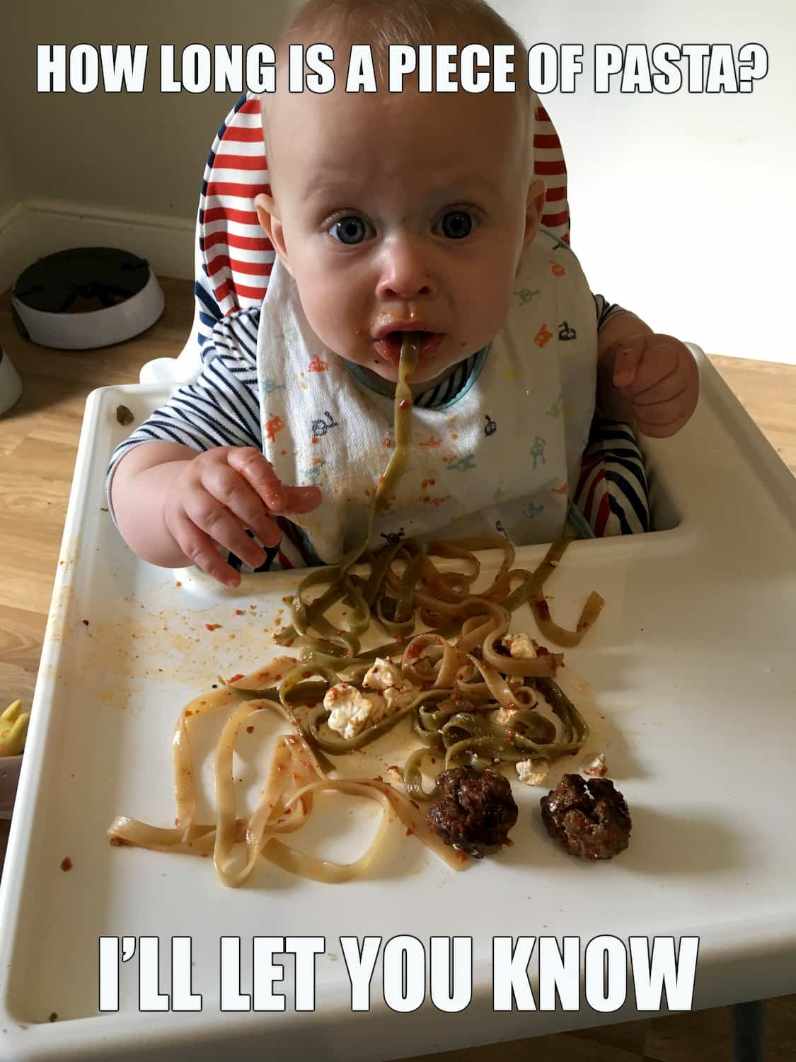 Photo of baby eating a long piece of pasta. Caption: how long is a piece of pasta? I'll let you know