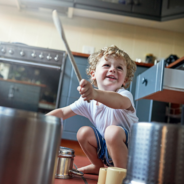 Photo of a toddler beating a pot as a drum