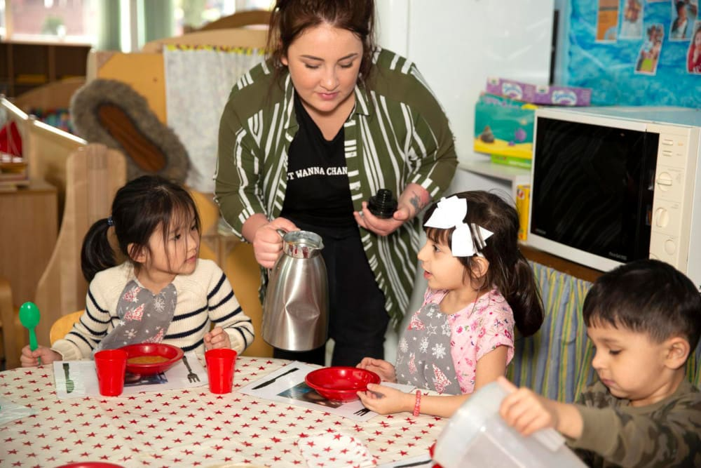 Image of an adult serving children tea at a table in a playroom.