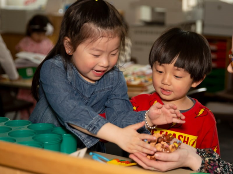 Image of two young children sitting at a table and playing with toys together.