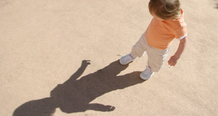 Photo of a child playing with their shadow