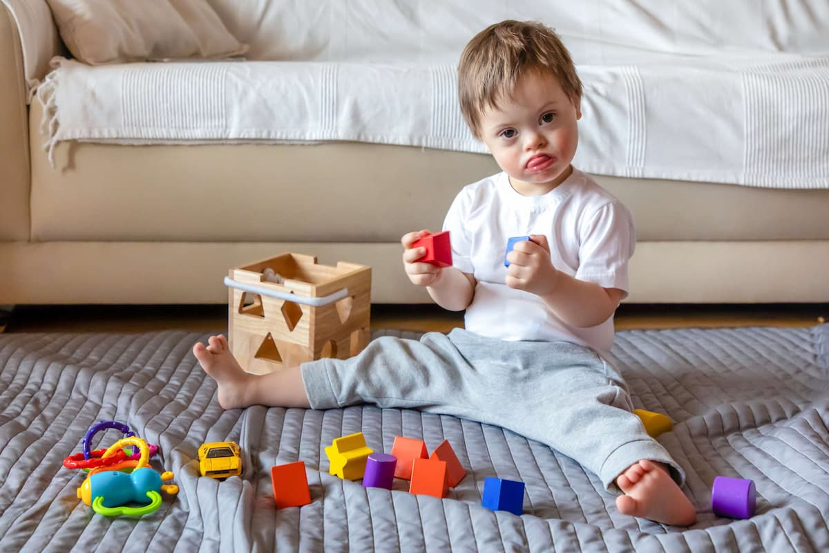 Photo of a baby boy sitting up and playing with blocks