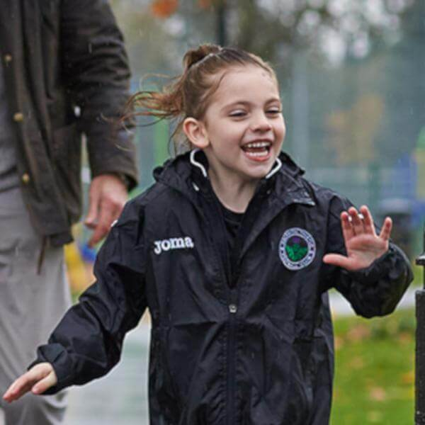 Photo of a child running through the rain the the park