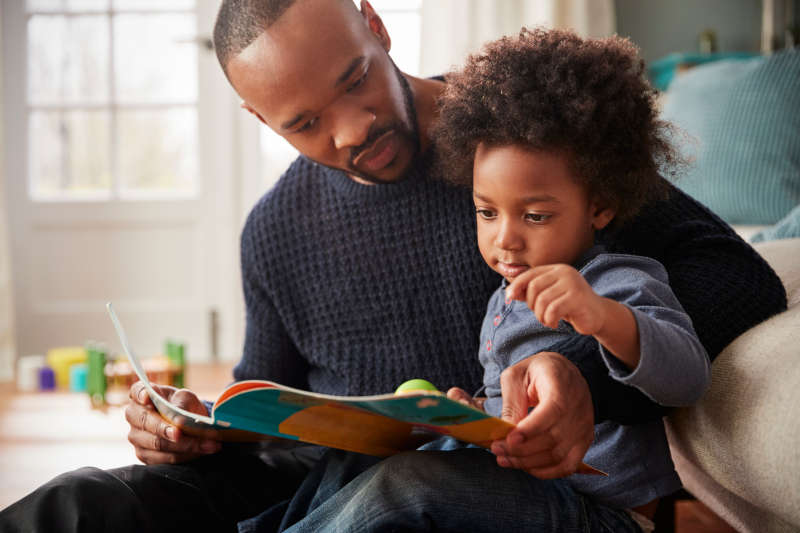 Image of a dad and child sitting together on a sofa reading a book.
