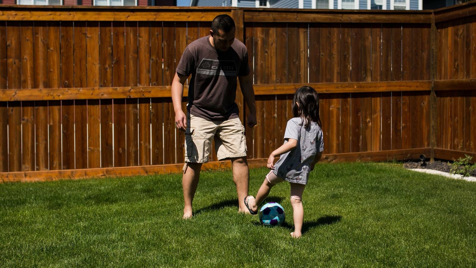 Image of a child and dad playing football in a garden.