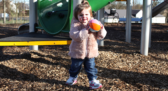 Photo of a toddler playing with a ball in a playground