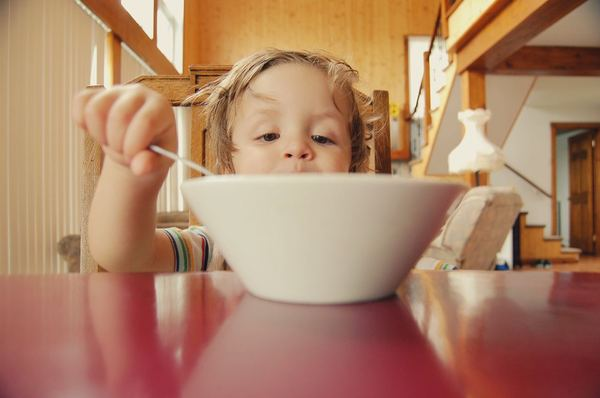 Photo of a child eating from a bowl